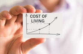 Closeup on businessman holding a card with COST OF LIVING rising arrow and chart business concept image with soft focus background